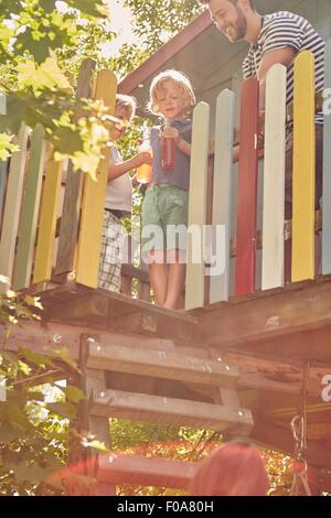 Father and sons in tree house, sons enjoying a drink - Stock Photo