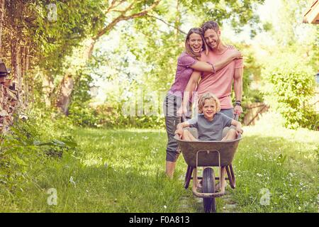 Portrait of young family, father pushing son in wheelbarrow - Stock Photo