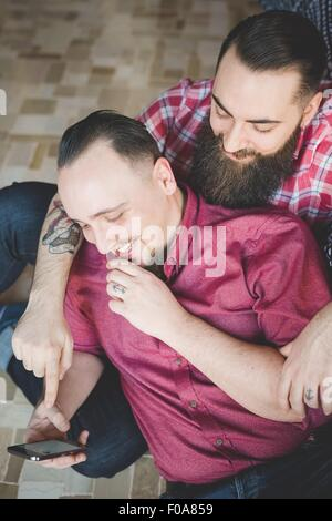 Gay couple using smartphone in bedroom - Stock Photo