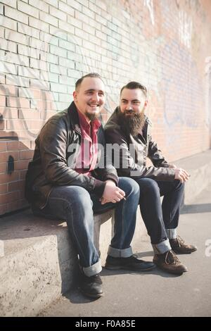 Gay couple sitting on concrete bench - Stock Photo