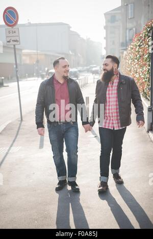 Gay couple walking hand in hand on street - Stock Photo