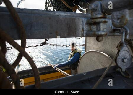 Fisherman preparing net reel - Stock Photo