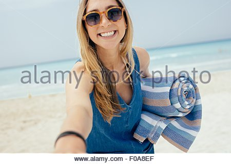 Portrait of young woman carrying picnic blanket on beach - Stock Photo