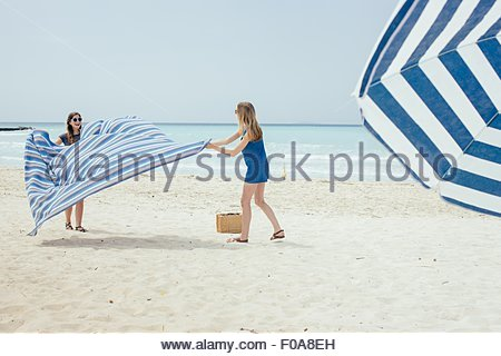 Two young female friends laying out picnic blanket on beach - Stock Photo