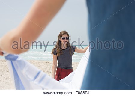 Cropped view of two young female friends laying out picnic blanket on beach - Stock Photo