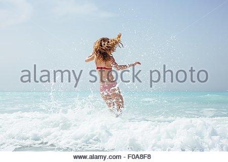 Rear view of young woman wearing bikini running in sea - Stock Photo