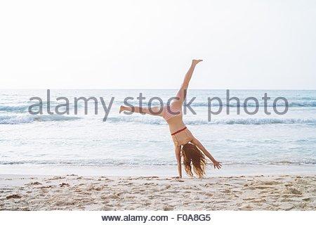 Young woman wearing bikini cartwheeling on beach - Stock Photo