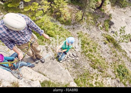 Father and children rock climbing, Ehrwald, Tyrol, Austria - Stock Photo