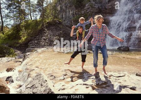 Two generation family having fun by waterfall, Ehrwald, Tyrol, Austria - Stock Photo