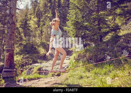 Woman balancing on rope, Ehrwald, Tyrol, Austria - Stock Photo