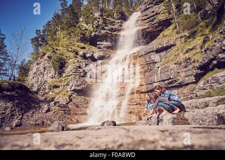 Mother and two children, exploring, beside waterfall - Stock Photo