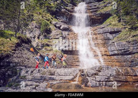 Group of children exploring by waterfall - Stock Photo