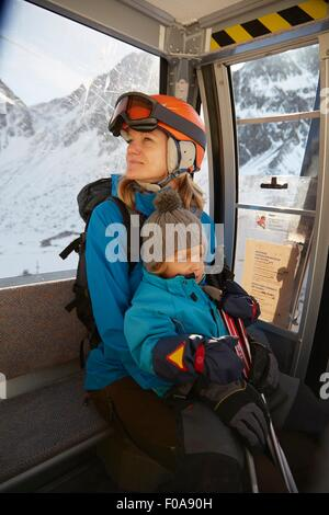 Mature female skier and toddler son sitting in ski lift, Neustift, Stubaital, Tirol, Austria - Stock Photo