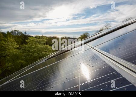 Elevated close up of sunlit solar panels on house roof - Stock Photo