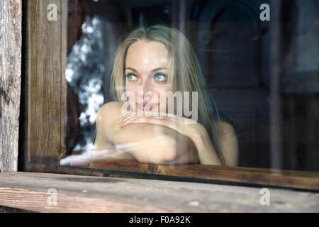 Young woman gazing from sauna window - Stock Photo