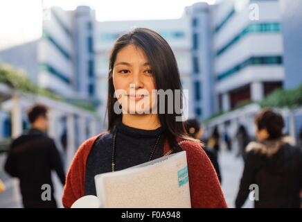 Portrait of young woman holding notebook looking at camera - Stock Photo