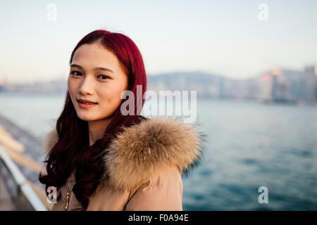 Portrait of young woman wearing fur trim coat with dyed red hair in front of water - Stock Photo
