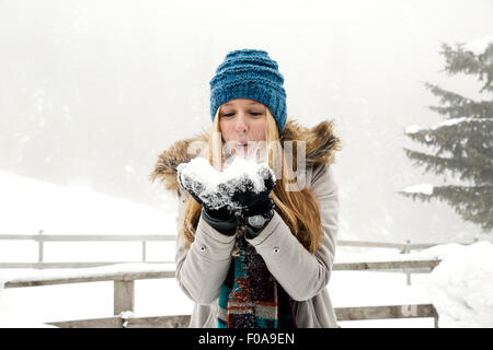 Young woman blowing handful of snow - Stock Photo