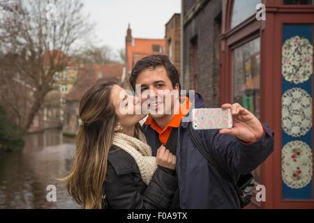 Couple taking selfie on smartphone, Bruges, Flanders, Belgium - Stock Photo