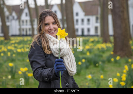 Portrait of young woman in spring park holding up daffodil - Stock Photo