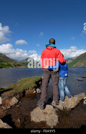 A father and son enjoy the view at Wastwater in the Lake District Cumbria, UK - Stock Photo