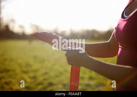 Cropped view of mature female boxer bandaging hands in field - Stock Photo