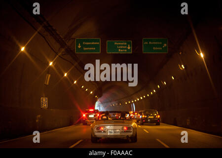 Two men in convertible car in tunnel, rear view - Stock Photo