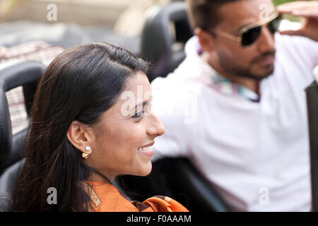 Mid adult couple in convertible car - Stock Photo