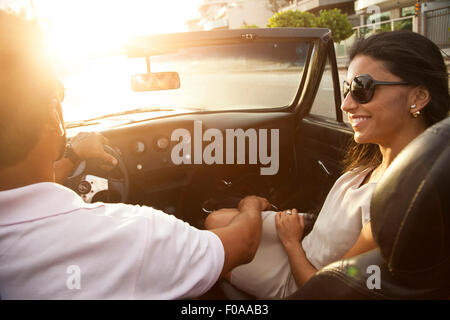 Mid adult couple in convertible car, rear view, close-up - Stock Photo