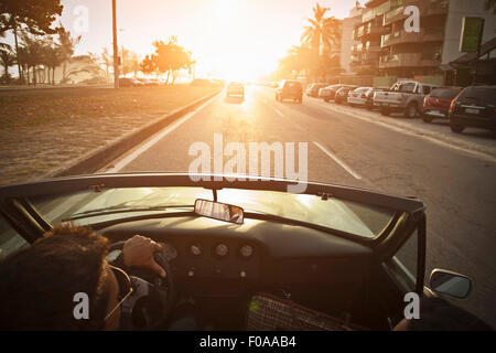 Mid adult man driving convertible car, elevated view - Stock Photo