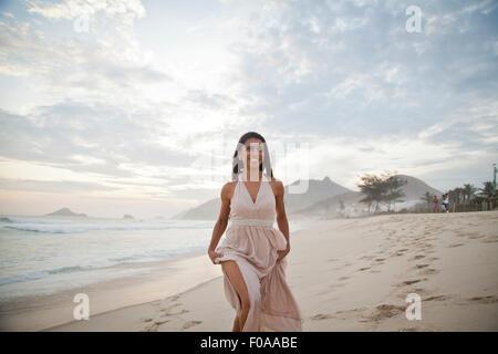 Mid adult woman walking along beach - Stock Photo