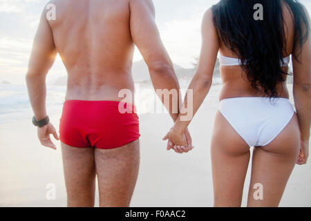 Mid adult couple standing on beach, hand in hand, wearing swimwear, rear view - Stock Photo