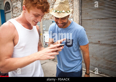 Two male friends looking at smartphone together - Stock Photo