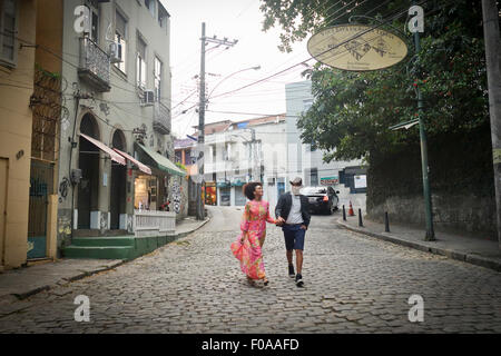 Couple walking down cobbled street, hand in hand - Stock Photo
