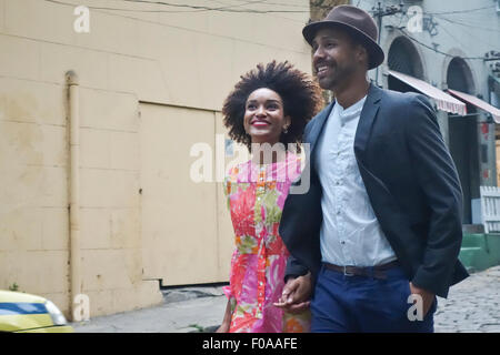 Couple walking down street, hand in hand - Stock Photo