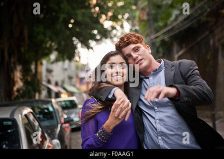 Couple walking along street, arms around each other, smiling - Stock Photo