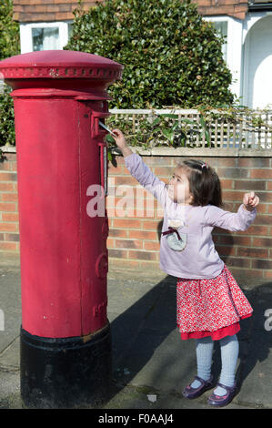 Young girl at post box, reaching up to post letter - Stock Photo