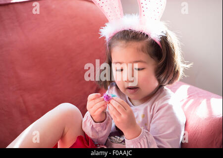 Young girl wearing bunny ears, looking at fluffy Easter chick - Stock Photo