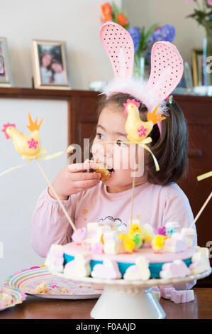 Young girl wearing bunny ears, eating cake - Stock Photo