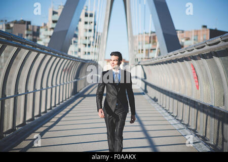 Young businessman crossing bridge - Stock Photo