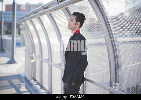 Young businessman by bridge safety fence - Stock Photo