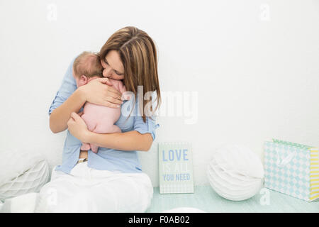 Mother cradling baby in arms - Stock Photo
