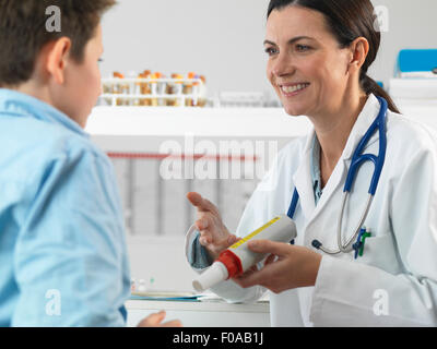 Doctor explaining lung function test to young boy in clinic - Stock Photo