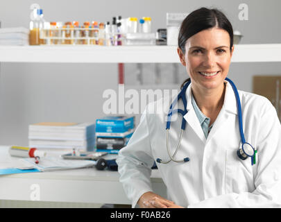 Doctor at desk awaiting patient - Stock Photo