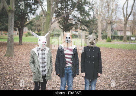 Three sisters wearing animal masks posing in park - Stock Photo