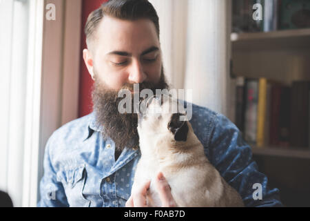 Young bearded man carrying dog in arms - Stock Photo