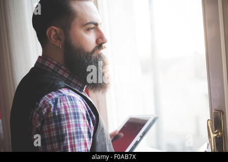 Young bearded man using digital tablet in room - Stock Photo