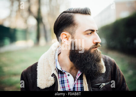Young bearded man in park - Stock Photo