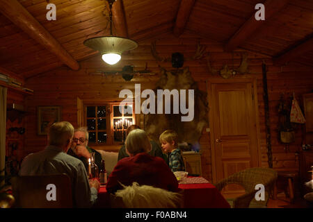 Three generation family sitting talking at Christmas table in log cabin at night - Stock Photo