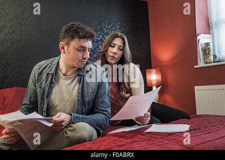 Couple on bed looking at paperwork - Stock Photo